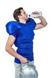 Hållande hjälm för amerikansk fotbollsspelare medan dricksvatten Fotografering för Bildbyråer