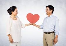 Hållande hjärta för romantiska par och seframsida - till - framsida arkivbild