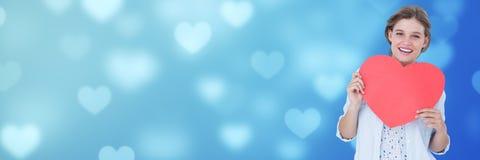 Hållande hjärta för valentinkvinna med förälskelsehjärtabakgrund Royaltyfria Foton