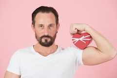 Hållande hjärta mot en bicepmuskel för dag för valentin` s Man och röda hjärtavisningmuskler och styrka som isoleras i studio arkivbild