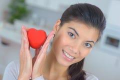 Hållande hjärtasymbol för kvinna i händer Arkivfoto