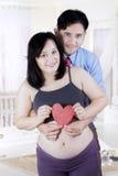 Hållande hjärtasymbol för lyckliga par royaltyfria bilder