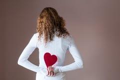 Hållande hjärtor för tonårig flicka bak henne tillbaka Arkivbilder