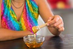 Hållande honungskopa för kvinna Arkivfoto