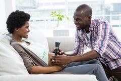 Hållande huvudtelefoner för man på gravid kvinnas mage Royaltyfri Foto