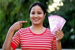 Hållande indier för ung kvinna 2000 rupieanmärkningar arkivbild