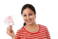 Hållande indier för ung kvinna två rupieanmärkningar royaltyfri foto