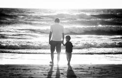 Hållande innehavhand för lycklig fader av den lilla sonen som tillsammans går på stranden med barfota Arkivbild
