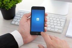 Hållande iPhone för affärsman 6 utrymmegrå färger med tjänste- LinkedIn Arkivfoton