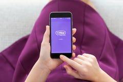 Hållande iPhone 6 för kvinna med Viber på skärmen Arkivfoto