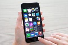 Hållande iPhone för kvinna 6 utrymmegrå färger över tabellen Royaltyfria Foton