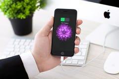 Hållande iPhone för man 6 utrymmegrå färger med batterisymbolen Royaltyfri Bild
