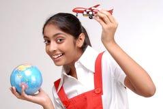 Hållande jordklot för indisk flicka och ett toyflygplan Royaltyfria Bilder