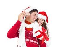 Hållande julgåva för festliga par royaltyfri fotografi
