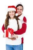 Hållande julgåva för festliga par arkivbilder