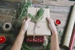 Hållande julklappar för man på trätabellbakgrund fotografering för bildbyråer
