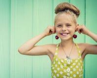 Hållande körsbär för den härliga flickan som örhängen - utforma Rockabilly royaltyfri foto