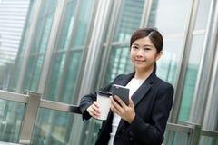 Hållande kaffe för affärskvinna och hennes mobiltelefon utanför kontor Royaltyfri Foto