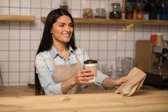 Hållande kaffe för servitris som går ta bort mat i kafé arkivbild