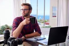 Hållande kaffe för ung fotograf på hans arbetsskrivbord Royaltyfri Fotografi