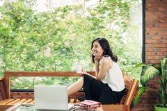 Hållande kaffekopp för asiatisk kvinna, medan sitta nära fönster i crea Arkivbilder