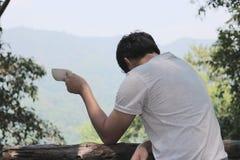 Hållande kaffekopp för frustrerad stressad man i hans händer i naturbakgrund arkivbilder