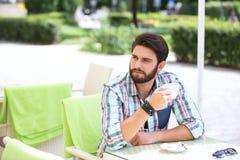 Hållande kaffekopp för fundersam man på trottoarkafét royaltyfri bild