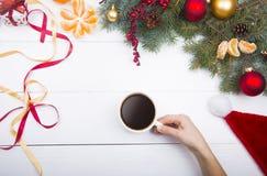 Hållande kaffekopp för hand på julpyntbakgrund Fotografering för Bildbyråer
