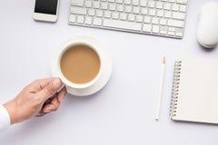 Hållande kaffekopp för manlig hand på den vita moderna funktionsdugliga tabellen Fotografering för Bildbyråer