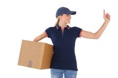Hållande kartong för lycklig leveranskvinna och peka upp Arkivbild