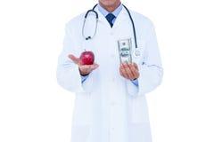 Hållande kassa för doktor och rött äpple royaltyfria foton