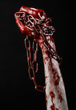 Hållande kedja för blodig hand, blodig kedja, halloween tema, svart bakgrund som isoleras Royaltyfri Fotografi