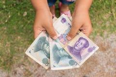 Hållande kinesiska pengar för unge Arkivfoton