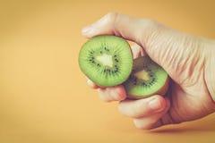 Hållande kiwifruit för hand arkivbild