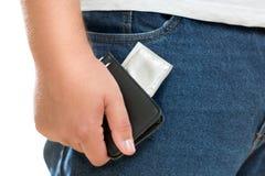Hållande kondom för ung man i plånbok Royaltyfri Foto
