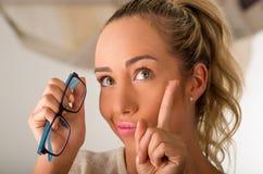 Hållande kontaktlins för ung blond kvinna på fingret som är främst av hennes framsida och innehav i hennes annan hand per blåa ex royaltyfri fotografi