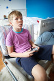 Hållande kontrollant Playing Video Game för pojke Royaltyfria Bilder