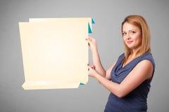 Hållande kopierar den pappers- vitorigamien för den unga kvinnan utrymme Arkivfoto