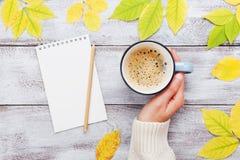 Hållande kopp kaffe för kvinnahand, öppen anteckningsbok och höstsidor på bästa sikt för tappningträtabell Hemtrevlig frukost royaltyfria foton