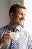 Hållande kopp kaffe för lycklig affärsman arkivfoto