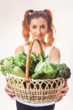 Hållande korg Beuatiful för caucasian flicka av isolerade nya rå gröna grönsaker Arkivbilder