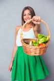 Hållande korg för kvinna med grönsaker royaltyfria foton