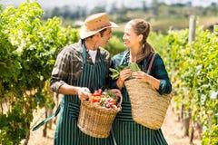 Hållande korgar för lyckliga bondepar av grönsaker Arkivbild