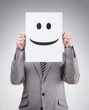 Hållande kort för affärsman med smileyframsidan fotografering för bildbyråer