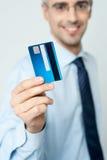Hållande kreditkort för gladlynt affärsman arkivfoton