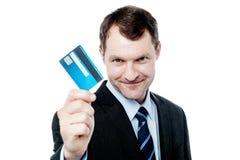 Hållande kreditkort för gladlynt affärsman royaltyfri foto