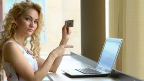 Hållande kreditkort för härlig kvinna i hand och shower hans finger på anteckningsboken arkivfilmer