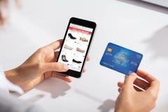 Hållande kreditkort för kvinna i handen som gör online-shopping arkivfoto