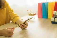 Hållande kreditkort för kvinna och användasmartphone för att shoppa onli royaltyfri foto