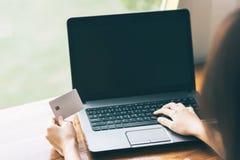 Hållande kreditkort för kvinnahand och användabärbar dator för online-affär Arkivbild